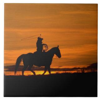 lariatロープとの日没のカウボーイの乗馬 タイル