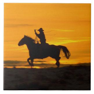 lariatロープ2との日没のカウボーイの乗馬 タイル