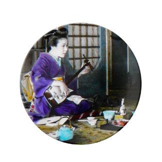 Shamisenのバンジョーを演奏しているヴィンテージの日本のな芸者 磁器プレート
