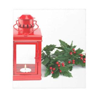 tealightのヒイラギの小枝および果実が付いている赤いランタン ノートパッド