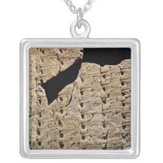 Urukからの楔形の原稿が付いているタブレット、 シルバープレートネックレス